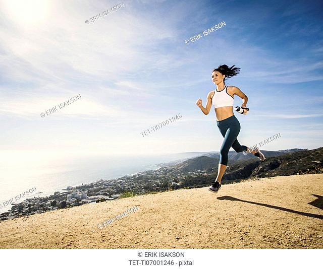Woman jogging on mountain with water bottle