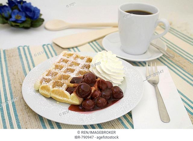 Waffle topped with powdered sugar, cherries and whipped cream served with a cup of coffee