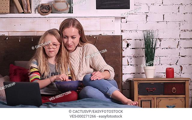 Mother and daughter watching cartoons on laptop
