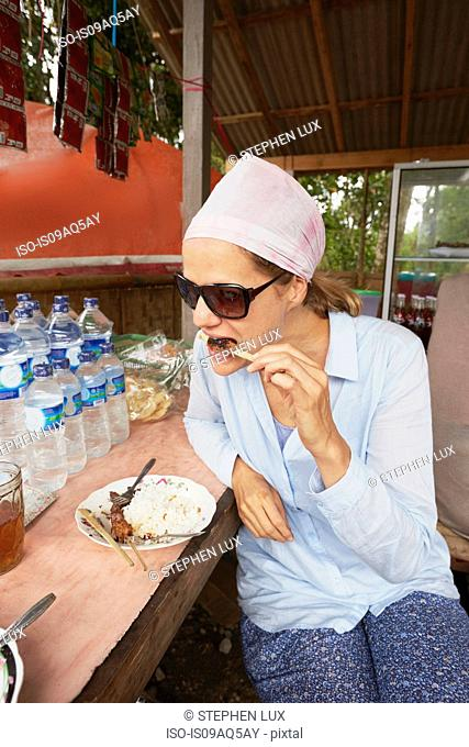 Mid adult woman eating snack at food stall, Bali, Indonesia