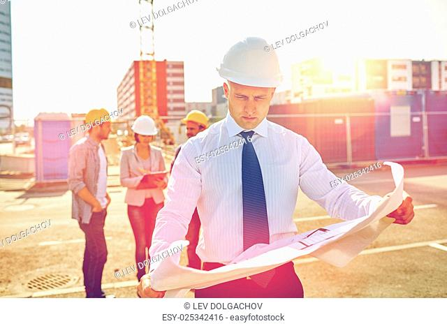 construction, architecture, business, teamwork and people concept - male architect with blueprint over group of builders on construction site