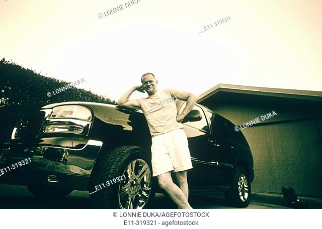 Man posing in front of new SUV