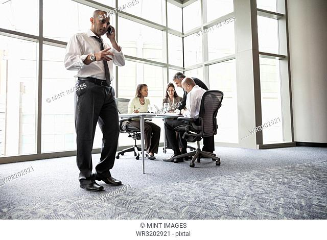 A middle eastern businessman on the phone during a meeting