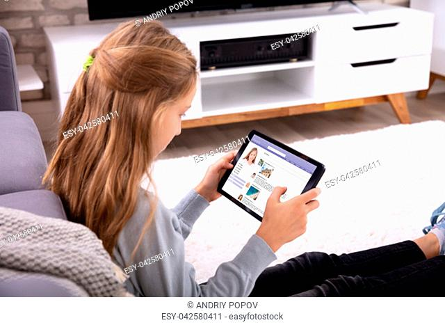 Close-up Of A Girl Using Social Networking Site On Digital Table At Home