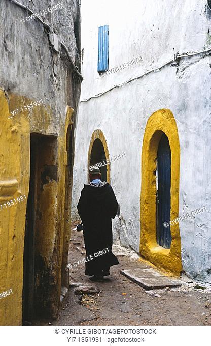 Man walking in narrow alley, Essaouira, Morocco