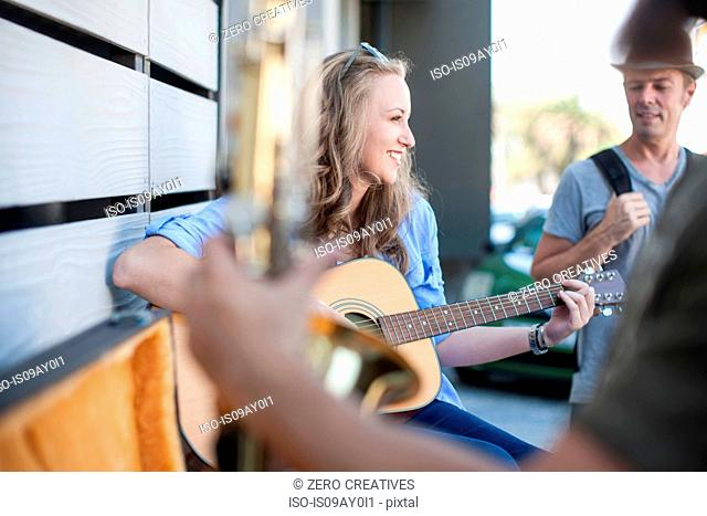 Female street musician, playing guitar