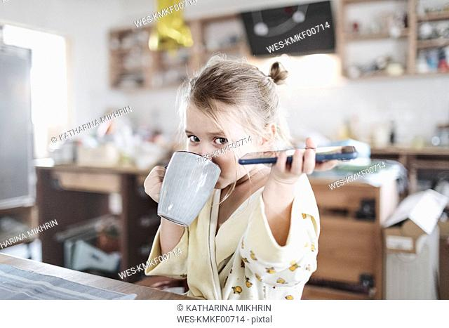 Portrait of little girl with smartphone drinking tea in the kitchen