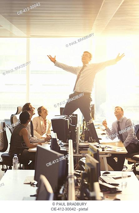 Colleagues watching exuberant businessman celebrating on top of desks in office