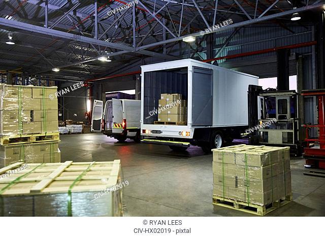 Trucks and cardboard box pallets at distribution warehouse loading dock