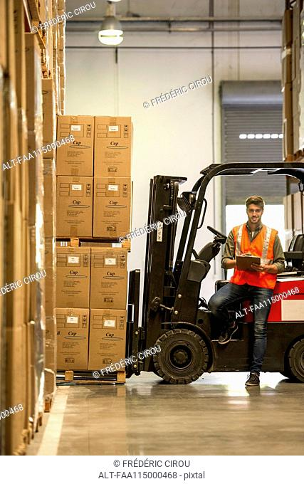 Worker standing with clipboard in warehouse