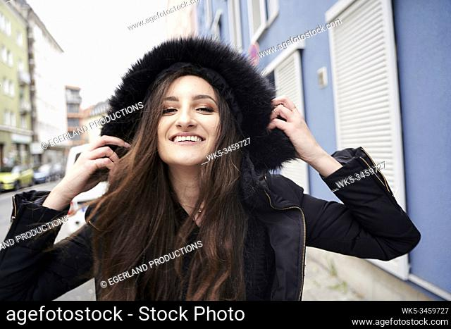 Young woman in hooded jacket. Munich, Germany