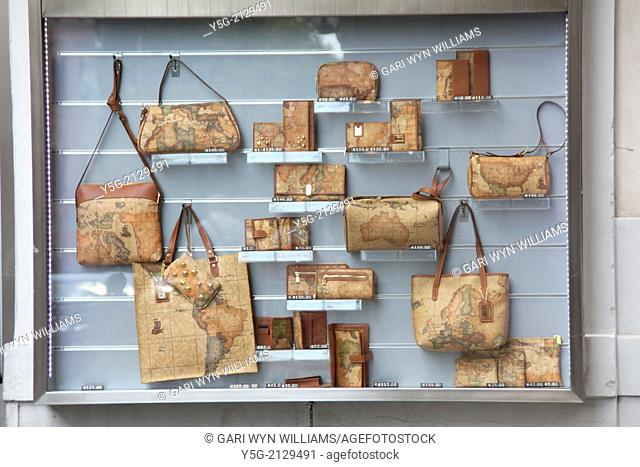 world map handbags on display in shop window in rome italy