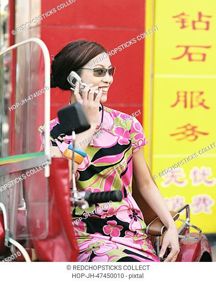 Young woman sitting on a pedicab and talking on a mobile phone
