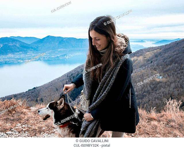 Woman walking dog on hilltop, Premeno, Piemonte, Italy
