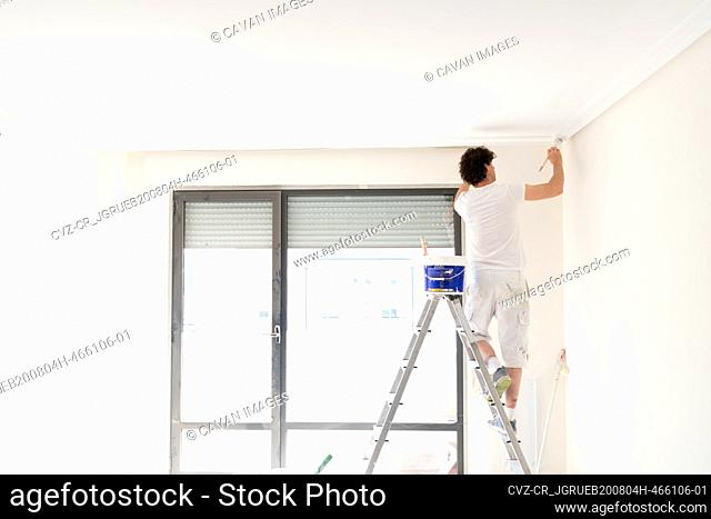 Worker painter painting the interior of a house on a staircase