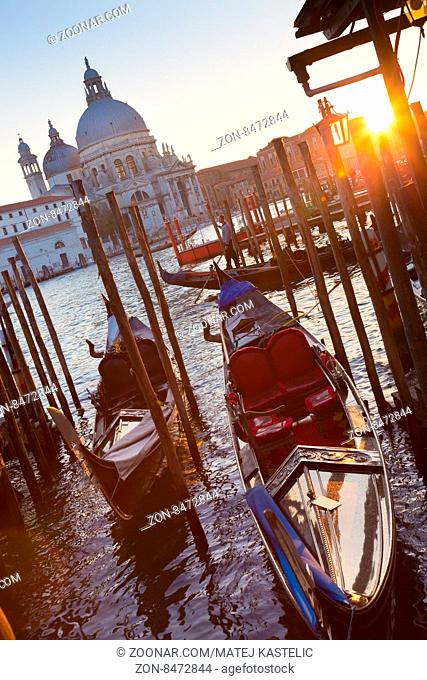 Venice, Italy - October 31, 2014: Traditional wooden boads and a gondolier in the Grand Canal in front of Santa Maria della Salute in sunset