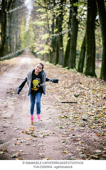 Girl runs along an avenue of lime trees in autumn