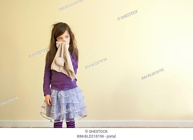 Sick Caucasian girl wiping nose