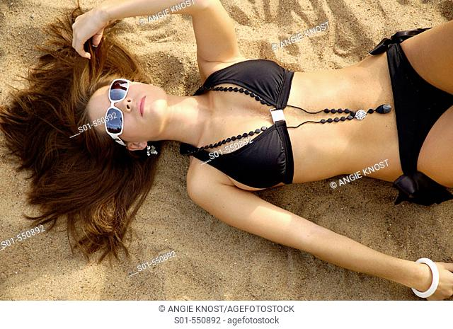 Attractive upscale woman, lying on beach.  She is wearing sunglasses, necklace, and bracelet with her black bikini, and is holding her hair