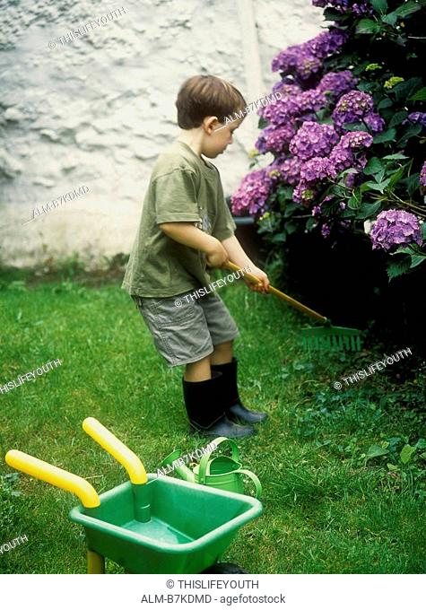 Young boy playing with a rake in a garden