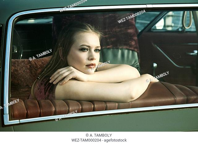 Portrait of young woman looking through rear window of vintage car