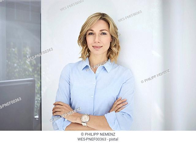 Portrait of blond woman, business woman, light blue blouse
