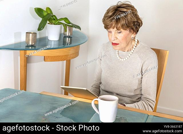 EIghty year old elegant woman reading her ipad