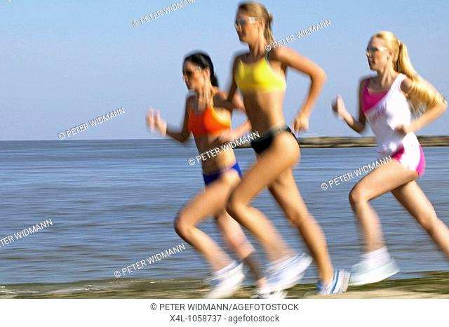 A group of young women jogging on the beach