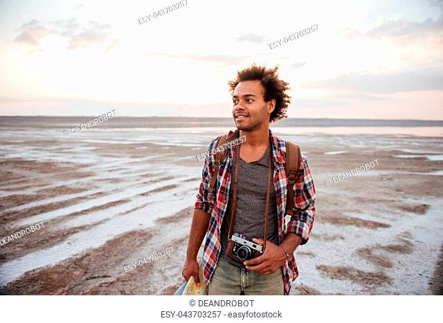 Happy curly african young man with backpack and old vintage camera walking on the beach