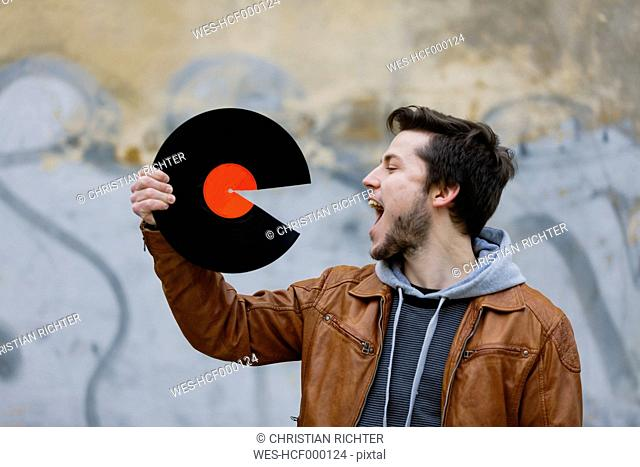 Young man holding broken record