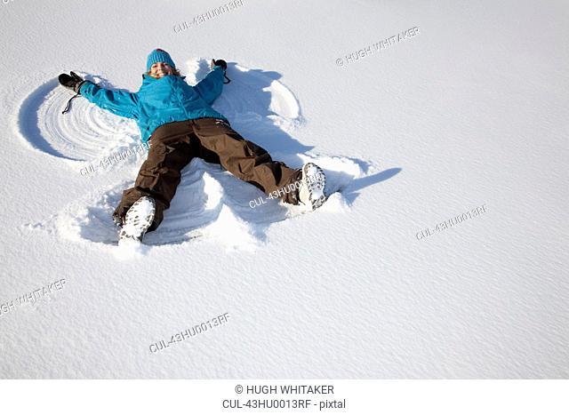 Woman making snow angel on field