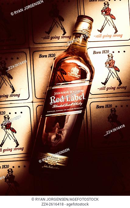 Johnnie Walker Red Label blended whisky sitting under a beam of light in a luxury night bar on a collection of advertisement coasters