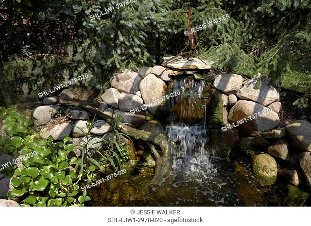 GARDENS: Pond with waterfall feature, larger view of pond with rusted Blue Heron sculpture ontop of the rocks