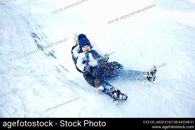 Mother and child tobogganing in winter