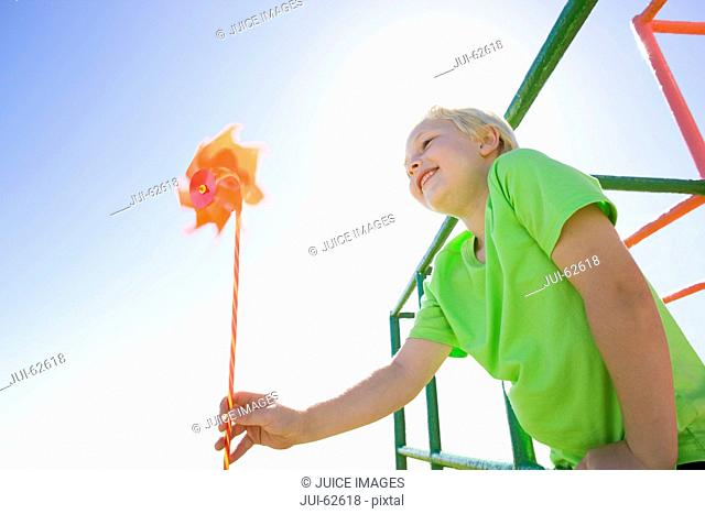 Boy playing with pinwheel on monkey bars at playground
