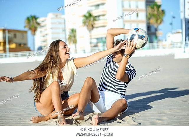Happy young couple sitting on the beach playing with a ball