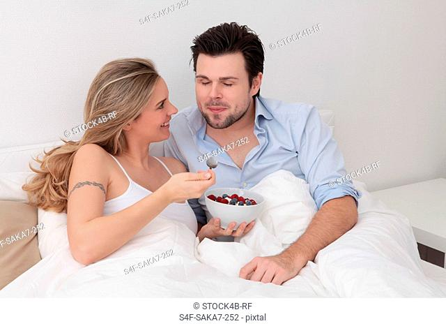 Couple eating berries from bowl in bed