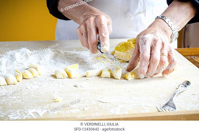 Italian chef cutting fresh homemade potato gnocchi into cubes with white flour on wooden board