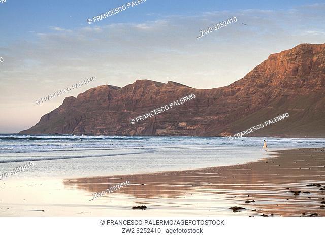 Sunset in the shore of a beach with persons walking along the shore of the sea. Famara, Lanzarote. Spain