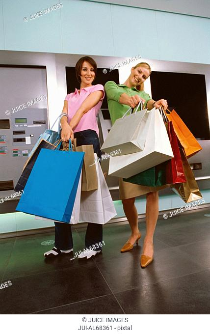 Two young women holding out shopping bags