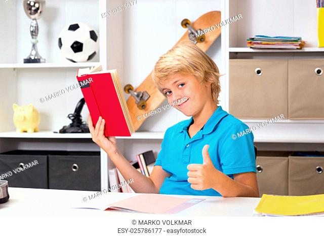 blond boy with thumb up doing homework and reading a book