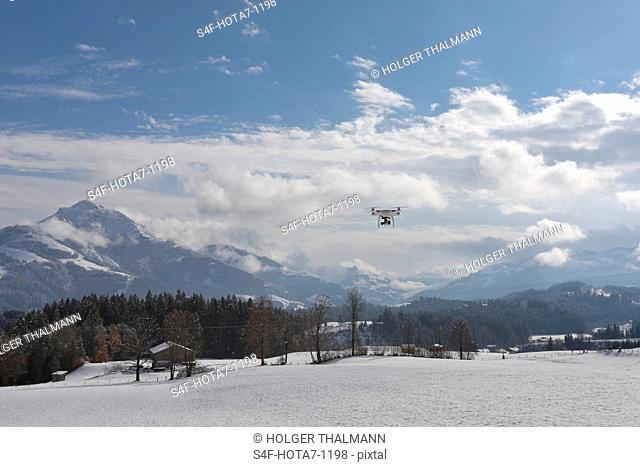 Österreich, Tirol, Wilder Kaiser, Drohne fliegt in Winterlandschaft