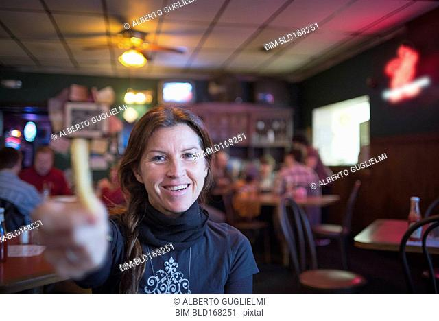 Caucasian woman offering french fry in bar