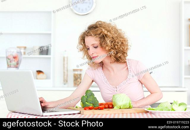 Pretty blonde woman relaxing with her laptop while cooking some