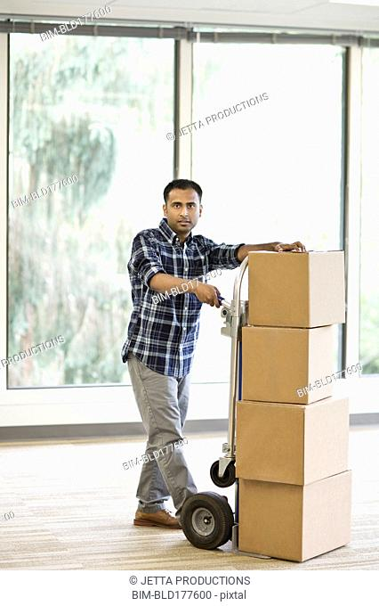 Mixed race businessman with boxes in empty office