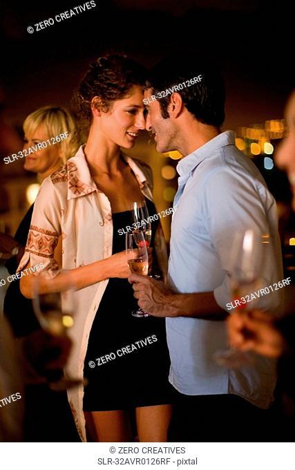 Couple having wine on terrace at night