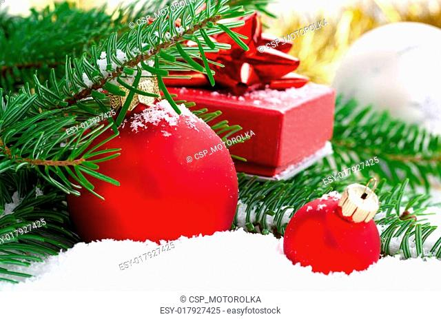red Christmas ball with pine branch, gift and snow, isolated on white background