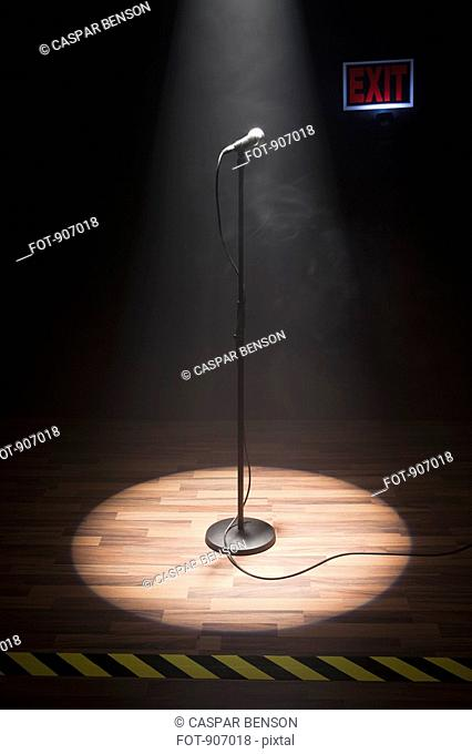 A Microphone Illuminated On A Stage