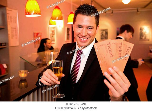 Handsome man in a theatre, concert or cinema presenting tickets