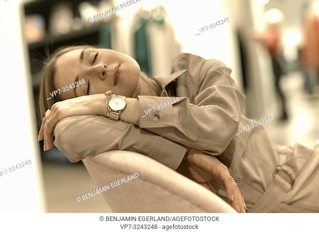 exhausted fashionable woman relaxing in armchair, sleepy, closed eyes, tired, in Munich, Germany